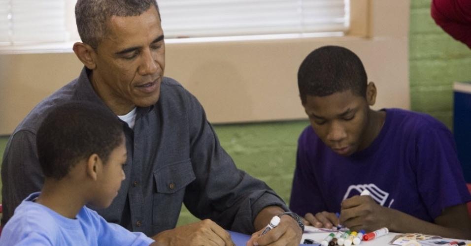 19.jan.2015 - O presidente dos Estados Unidos, Barack Obama, trabalha em um projeto de alfabetização com crianças no