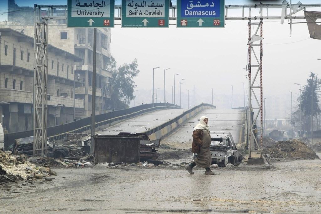 20.jan.2015 - Cidadão sírio atravessa a estrada Al-Haj, que foi fechada por franco-atiradores das forças leais ao ditador Bashar Al-Assad, em Aleppo, nesta terça-feira (20)