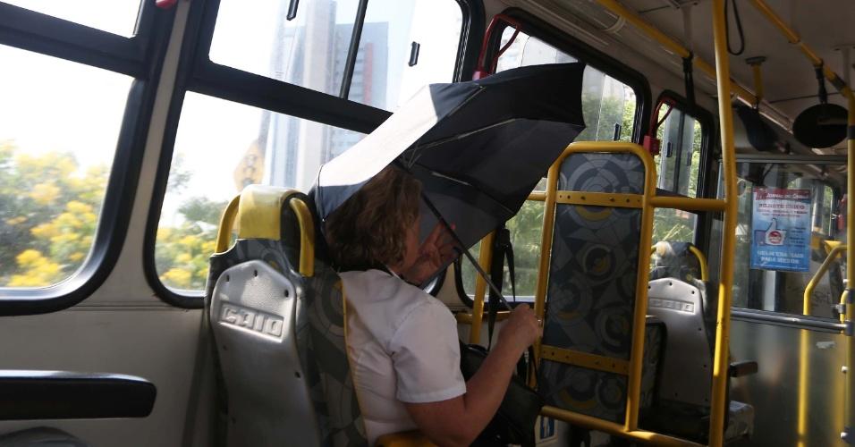 20.jan.2015 - Passageira abre sombrinha dentro do ônibus para se proteger do sol na zona sul de São Paulo, nesta terça-feira. De acordo com a Somar Meteorologia, os termômetros chegaram a atingir 35,6°C, por volta das 16h, no mirante de Santana, na zona norte. Com isso, a capital paulista chega a 15 dias seguidos registrando temperaturas acima dos 30°C