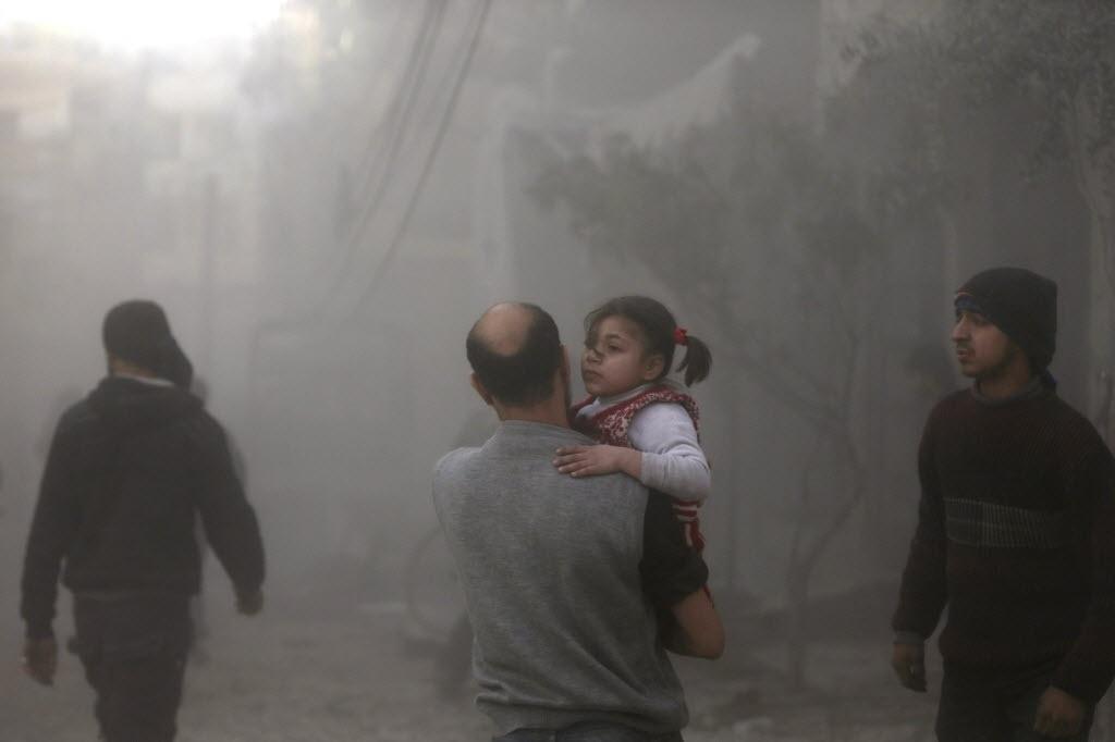 21.jan.2015 - Moradores fogem de uma construção danificada após dois ataques aéreos feitos pelas forças leais ao ditador sírio Bashar Assad em Ghouta, perto de Damasco, nesta quarta-feira (21)