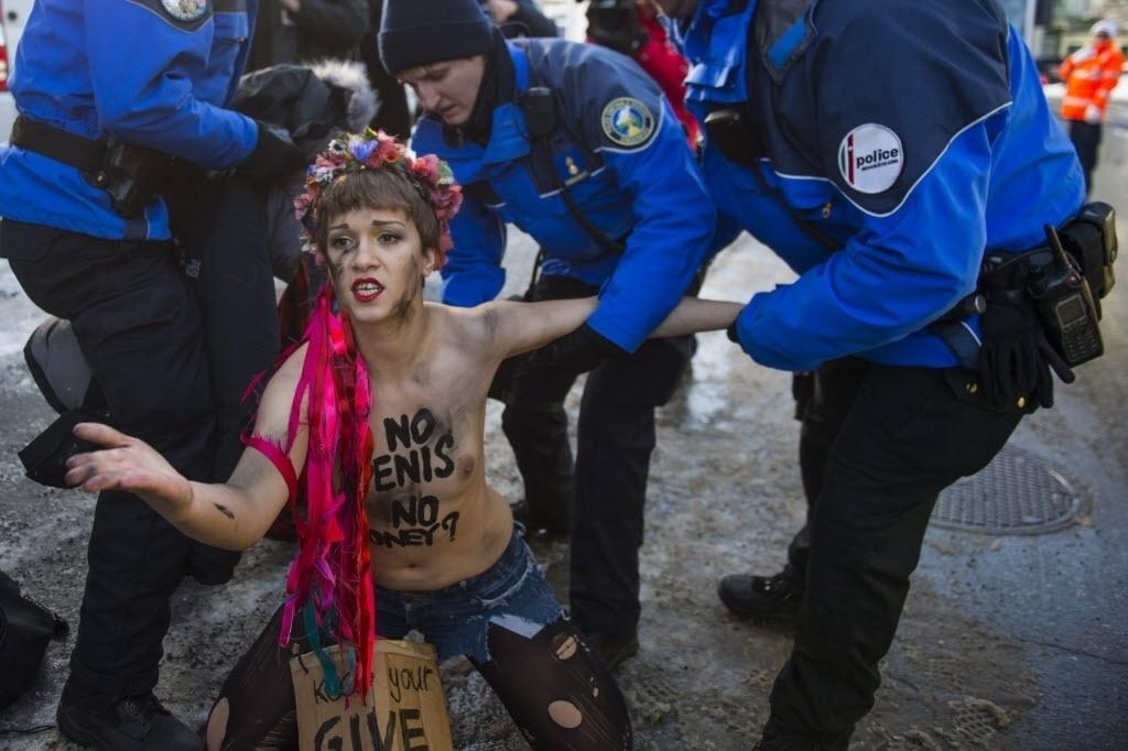 22.jan.2015 - Uma ativista do grupo feminista Femen é detida por policiais durante a celebração da 45ª edição do Fórum Econômico Mundial, em Davos, na Suíça. O evento reúne mais de 40 chefes de Estado e de governo e empresários de diversos setores durante quatro dias de debates