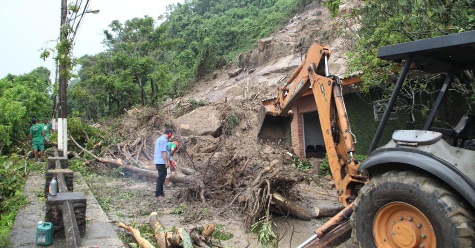 23.jan.2015 - Funcionários trabalham nesta sexta-feira (23) na limpeza de via após deslizamento de terra e quedas de árvores no bairro Morro Santa Teresinha, na cidade de Santos. Segundo a Defesa Civil da cidade, choveu em 10 horas mais do que o esperado para o mês de janeiro