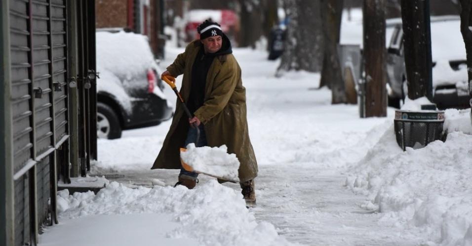 27.jan.2015 - Americano usa uma pá para retirar neve acumulada na calçada, no Bronx, bairro de Nova York (EUA). Milhões de americanos foram afetados ao longo da costa nordeste depois de uma tempestade de neve paralisar Nova York e outras grandes cidades