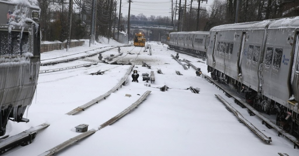 27.jan.2015 - Trens da companhia Long Island ficam estacionados enquanto um vagão de manutenção percorre a linha de Port Washington, em Nova York (EUA). Uma nevasca varreu o nordeste dos Estados Unidos, acumulando mais de 30 cm de neve nas ruas. Trabalhadores e estudantes ficaram em casa após autoridades proibirem carros nas estradas e fecharem os trens do metrô