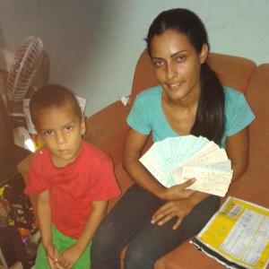 Ana Maurícia, ao lado do filho, mostra cheques encontrados no lixo