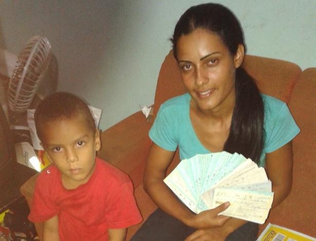 Ana Maurícia, ao lado do filho, mostra cheques encontrados no lixo; ela deve ganhar agora um novo emprego