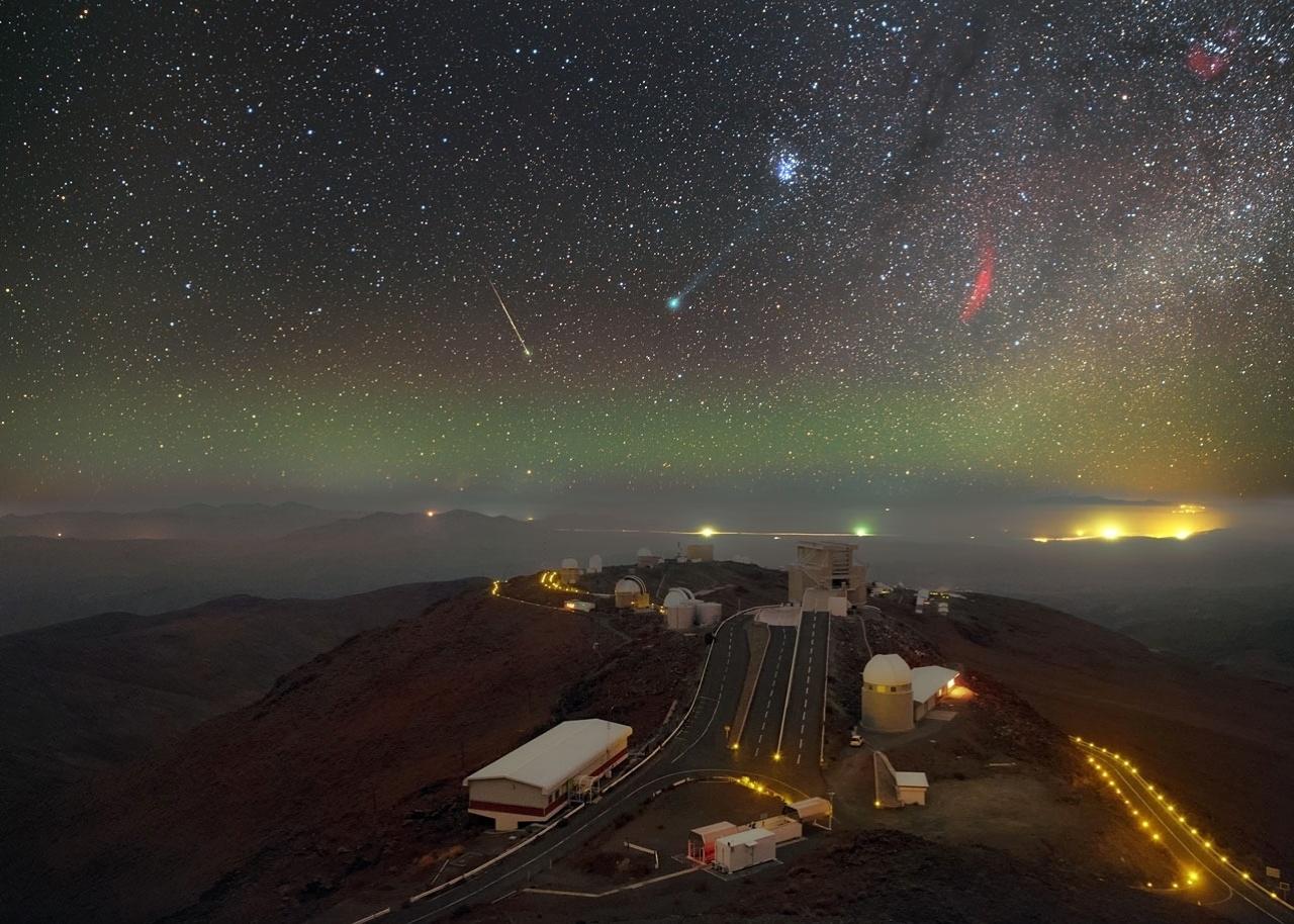 28.jan.2015 - Imagem fornecida pelo ESO (Observatório Europeu do Sul) exibe o cometa Lovejoy, brilhando verde no centro da imagem; as Plêiades (grupo de estrelas) em cima à direita; e a nebulosa Califórnia, que aparece sob a forma de um arco de gás vermelho à direita do cometa. O registro foi obtido no deserto do Atacama, no Chile, e esta foi a primeira vez em 11.000 anos que o Lovejoy passou no sistema solar interior
