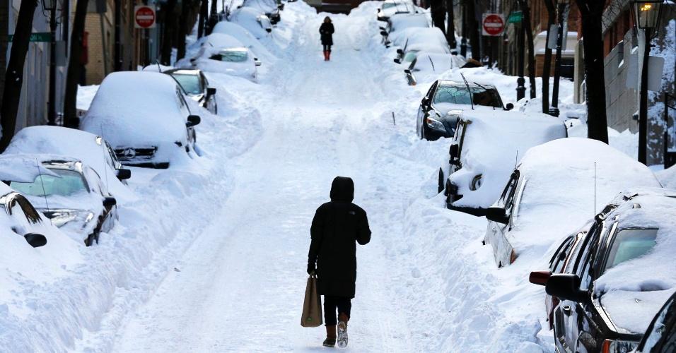 28.jan.2015 - Moradora caminha nesta quarta-feira (28) em rua coberta pela nevasca que atinge há dias a região de Boston, Estado de Massachusetts, nos Estados Unidos. Na terça-feira, a neve chegou a 67 centímetros na região e milhares de pessoas ficaram sem energia