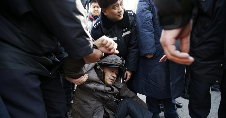29.jan.2015 - Familiar de passageiro que estava a bordo do voo MH370, da Malaysia Airlines, passa mal e é atendido por policiais durante um protesto que exige que o governo da Malásia continue a procurar a aeronave desaparecida em março de 2014, em frente à embaixada da Malásia em Pequim, na China. As autoridades malaias anunciaram que a aeronave sofreu um acidente fatal e que todos a bordo estão presumidamente mortos