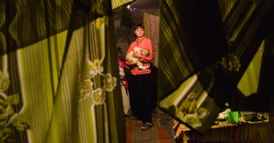 29.jan.2015 - Mãe carrega seu bebê em abrigo antiaéreo em Donetsk, no leste da Ucrânia. Famílias que moram no local receberam esta semana kits de higiene enviados pelo Comitê Europeu de Ajuda Humanitária e Proteção Civil (Echo, na sigla em inglês) e pela Unicef. Mais de 1,7 milhões de crianças afetadas pela crescente crise no leste do país sofrem risco de contrair várias doenças devido à falta de higiene