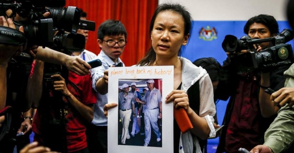 29.jan.2015 - Mulher de um dos passageiros do voo MH370, da Malaysia Airlines, mostra uma fotografia de seu marido durante uma conferência de imprensa em Putrajaya, na Malásia. As autoridades anunciaram que a aeronave, que desapareceu em março do ano passado, sofreu um acidente fatal e que todos a bordo estão presumidamente mortos