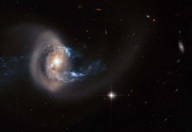 29.jan.2015 - O telescópio Hubble da Nasa (agência espacial americana) e da ESA (agência espacial europeia) captou a galáxia espiral NGC 7714 se fundindo com a NGC 7715. Uma névoa dourada que se estende para fora do centro da galáxia é resultado dessa fusão em curso
