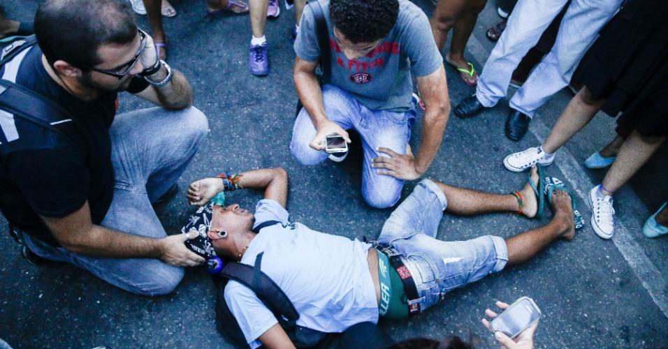 30.jan.2015 - Manifestantes acodem colega desacordado durante passeata contra o aumento das tarifas de transporte público próximo à Central do Brasil, no Rio de Janeiro. A manifestação começou na Candelária e seguiu em direção à Central do Brasil. Houve confronto entre manifestantes e policiais