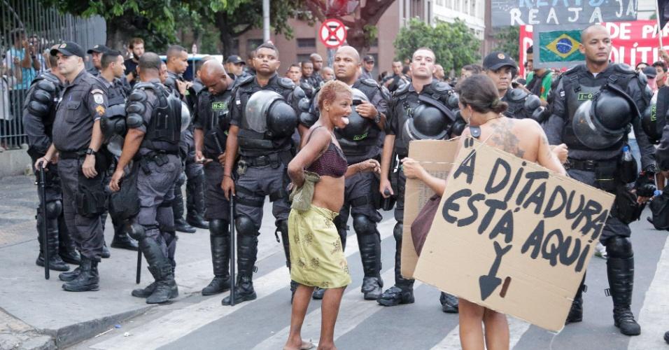 30.jan.2015 - Manifestantes exibem cartazes diante de policiais durante o protesto contra o aumento das tarifas de transporte público no Rio Janeiro. A manifestação começou na Candelária e seguiu em direção à Central do Brasil