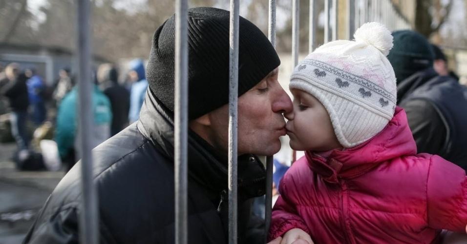 30.jan.2015 - Menina beija seu pai, um recruta do exército, depois de uma cerimônia que marcou a inscrição de novos recrutas para lutar pela Ucrânia, em Kiev, nesta sexta-feira (30). O Parlamento ucraniano decidiu aumentar suas forças da linha de frente e retomar o recrutamento depois que forças russas que apoiam rebeldes separatistas aumentaram a atividade militar no leste da Ucrânia