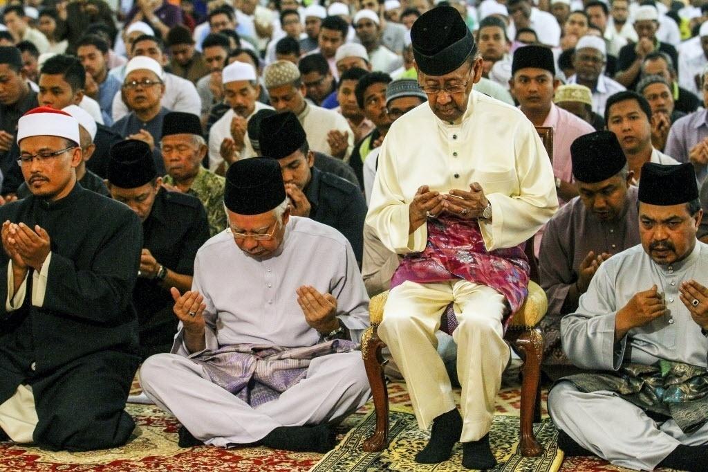 30.jan.2015 - O rei da Malásia, Abdul Halim Mu'adzam Shah (sentado na cadeira), e o primeiro-ministro Najib Razak (do lado esquerdo do rei), rezam pelos passageiros desaparecidos do voo MH730 da Malaysia Airlines em uma mesquita em Kuala Lumpur, nesta sexta-feira (30). A Malásia suspendeu as buscas pela aeronave, mas o governo australiano informou que continuará a procurar o avião que desapareceu no dia 8 de março de 2014 e apoiará as famílias dos 239 passageiros a bordo