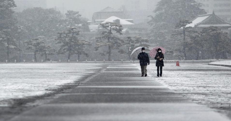 30.jan.2015 - Visitantes caminham pelo palácio imperial japonês enquanto neve cai em Tóquio, nesta sexta-feira (30). Após fortes nevascas na quinta, dezenas de voos domésticos foram cancelados, e as empresas calculam que mais voos com chegada ou partida em Tóquio devem ser cancelados nesta sexta