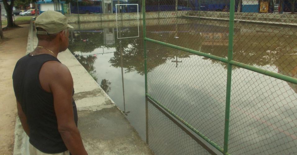 2.fev.2015 - Morador observa nesta segunda-feira (2) uma quadra de futebol que ficou inundada, na praça Saiqui, em Vila Valqueire, zona oeste do Rio de Janeiro, após a chuva de domingo