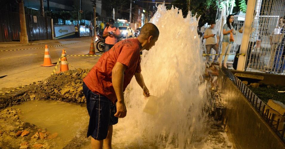 3.fev.2015 - Homem pega água em vazamento de cano estourado na rua Tamandaré, no bairro da Liberdade, no centro de São Paulo. A 'fonte' atinge cerca de 1,6 m de altura