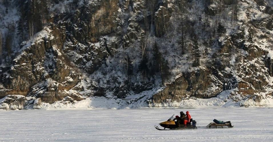 3.fev.2015 - Moradores usam uma moto de neve para se locomover sobre o rio Yenisei, que está congelado, perto da cidade siberiana de Krasnoyarsk, na Rússia, nesta terça-feira (3)