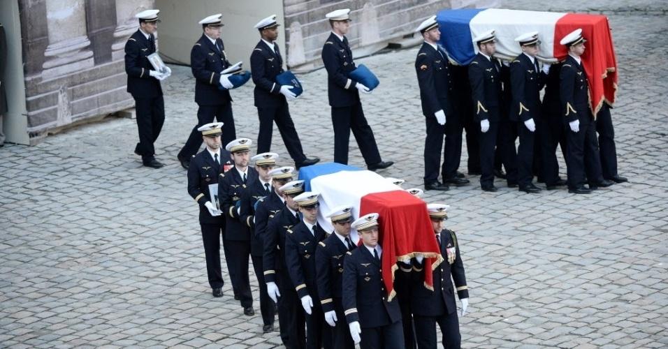 3.fev.2015 - Oficiais carregam caixões com bandeiras francesas durante uma cerimônia em Paris, nesta terça-feira (3), em honra dos nove soldados mortos em um acidente na Espanha em 26 de janeiro. O presidente François Hollande participou do funeral dos militares, mortos quando um jato F-16 grego caiu em uma base espanhola