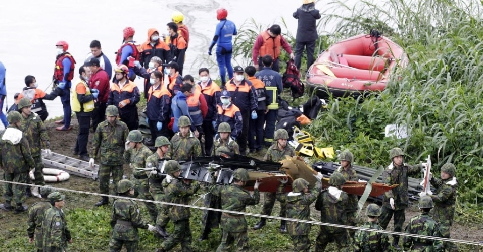 4.fev.2015 - Soldados removem partes de um avião da TransAsia que caiu em um rio em Taipé, Taiwan, Um avião que transportava 58 pessoas, bateu em uma ponte e caiu em um rio deixando mortos e feridos