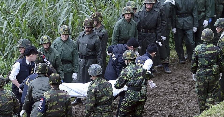 4.fev.2015 -Soldados carregam o corpo de uma vítima de um acidente aéreo em Taipé, Taiwan. Um avião que transportava 58 pessoas, bateu em uma ponte e caiu em um rio deixando mortos e feridos