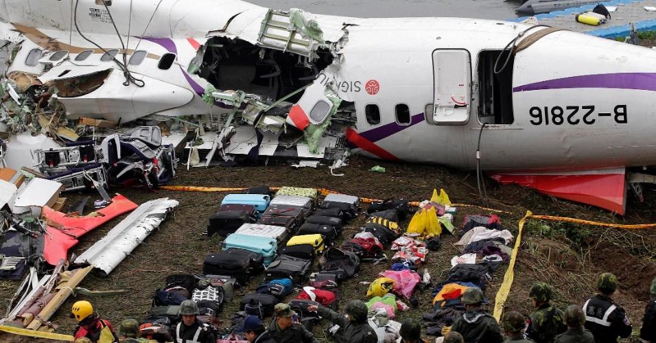 5.fev.2014 - Bagagens são colocadas junto dos destroços do avião da TransAsia Airways acidentado em Taipé (Taiwan) na quarta-feira, matando 31 pessoas. O número de vítimas fatais ainda pode subir, já que 12 pessoas ainda estão desaparecidas. O avião, transportando 58 pessoas, entre passageiros e tripulantes, caiu pouco depois de decolar, acertando ainda um carro ao bater em uma ponte