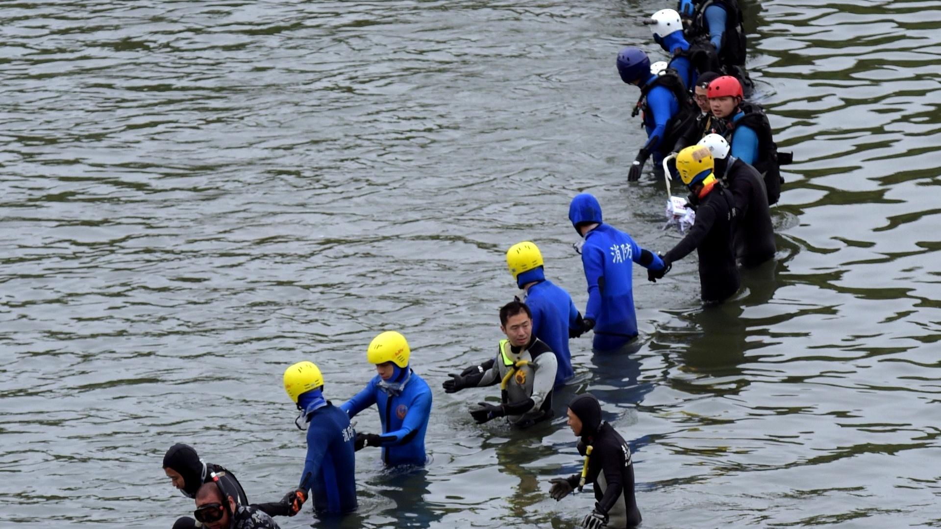 6.fev.2015 - Membros de equipes de resgate fazem nesta sexta-feira (6) corrente em busca dos passageiros ainda desaparecidos do acidente com o avião turboélice da TransAsia Airways no rio Keelung, em Taipé (Taiwan). O avião ATR 72-600 caiu pouco depois de decolar na última quarta-feira, com 58 pessoas a bordo. Ao menos 31 pessoas morreram no acidente, e 12 continuavam desaparecidas na madrugada desta sexta