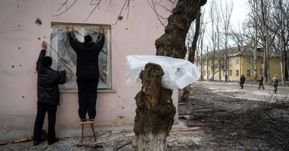 7.fev.2015 - Moradores usam lonas de plástico para substituir janela quebrada após ataques na cidade de Vuglegirsk, região de Donetsk, no leste da Ucrânia. As autoridades ucranianas afirmaram que há razões para ser otimista sobre um acordo de paz com a Ucrânia, mas também alertou contra iniciativas para armar o exército de Kiev, e culpou os Estados Unidos e a Europa por
