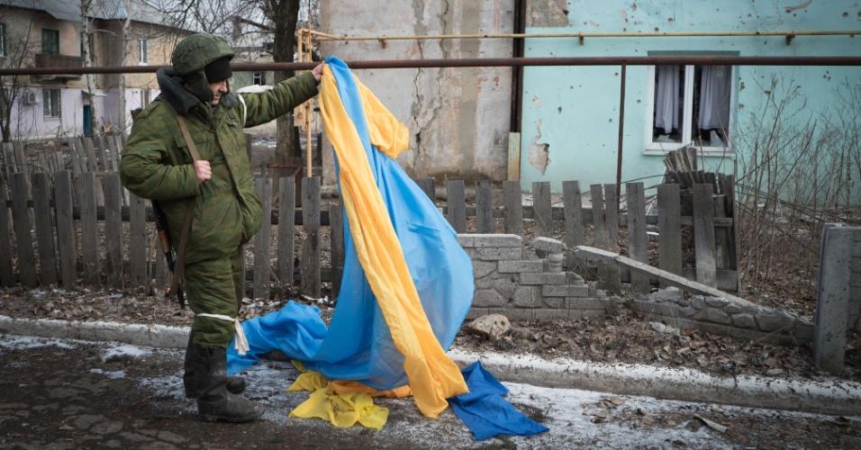 7.fev.2015 - Um rebelde pró-Rússia recolhe bandeira ucrânia em rua de Vuglegirsk, na região de Donetsk, no leste da Ucrânia. As autoridades ucranianas afirmaram que há razões para ser otimista sobre um acordo de paz com a Ucrânia, mas também alertou contra iniciativas para armar o exército de Kiev, e culpou os Estados Unidos e a Europa por