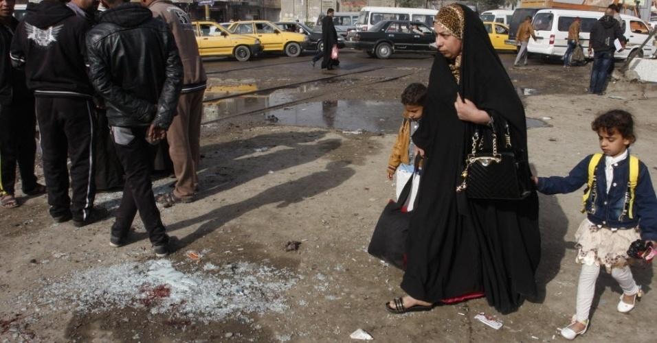 9.fev.2015 - Mulher com crianças passam em local de ataque suicida no bairro de Kadhimiyah, em Bagdá, no Iraque, nesta segunda-feira (9). Pelo menos 15 pessoas ficaram feridas no atentado