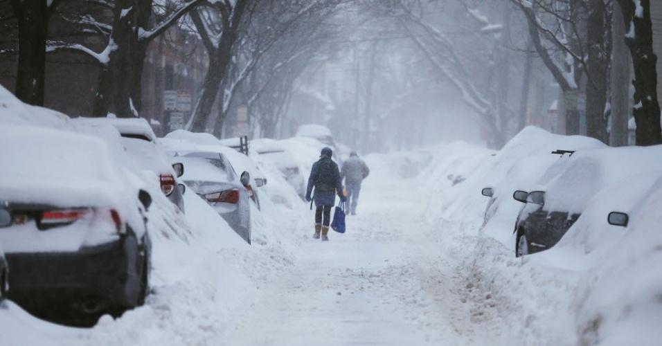 9.fev.2015 - Pedestres caminham nesta segunda-feira (9) por rua coberta de neve durante uma tempestade em Cambridge, no Estado americano de Massachusetts. Boston e outras áreas do nordeste do país já acumulam cerca de um metro de neve em 10 dias