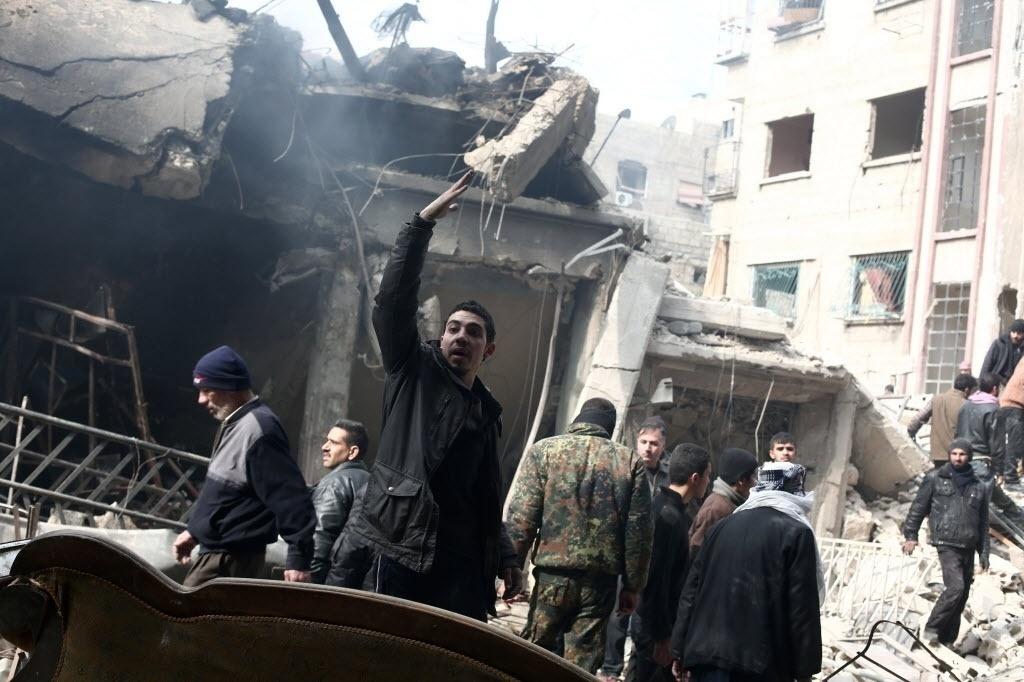 9.fev.2015 - Sírios procuram por sobreviventes no local onde aconteceram ataques aéreos feitos por forças do regime de Bashar Assad, em Douma, área controlada pelos rebeldes, nesta segunda-feira (9). Milhares de moradores isolados na região sofrem com a escassez de alimentos e médicos