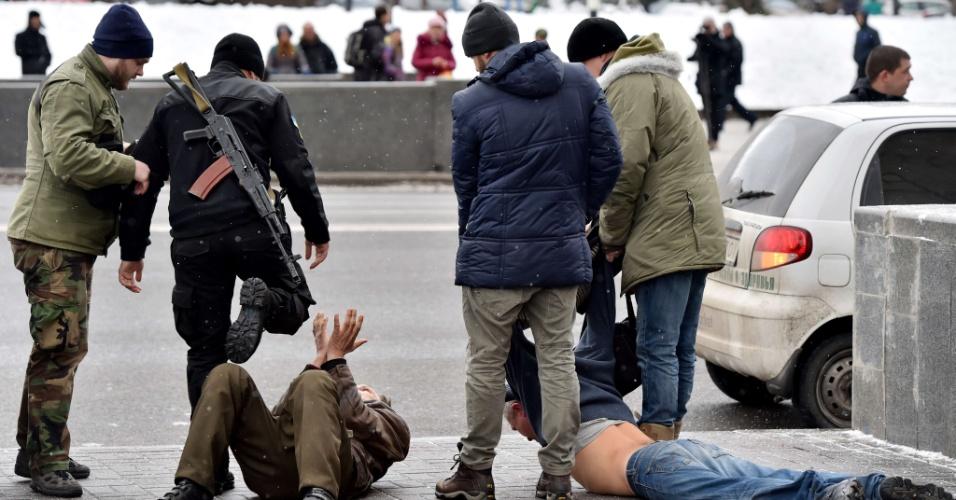 9.fev.2015 - Patrulha composta por integrantes do batalhão de voluntários ucranianos e policiais detém dois homens na praça da Independência, em Kiev, nesta segunda-feira (9). Os detidos supostamente chegaram de Donetsk, no leste do país, e são suspeitos de participarem de atividades separatistas e organizarem ataques terroristas na capital da Ucrânia. Ao menos 1.500 tropas russas e 300 equipamentos militares entraram na Ucrânia durante o fim de semana, segundo fontes do Exército ucraniano