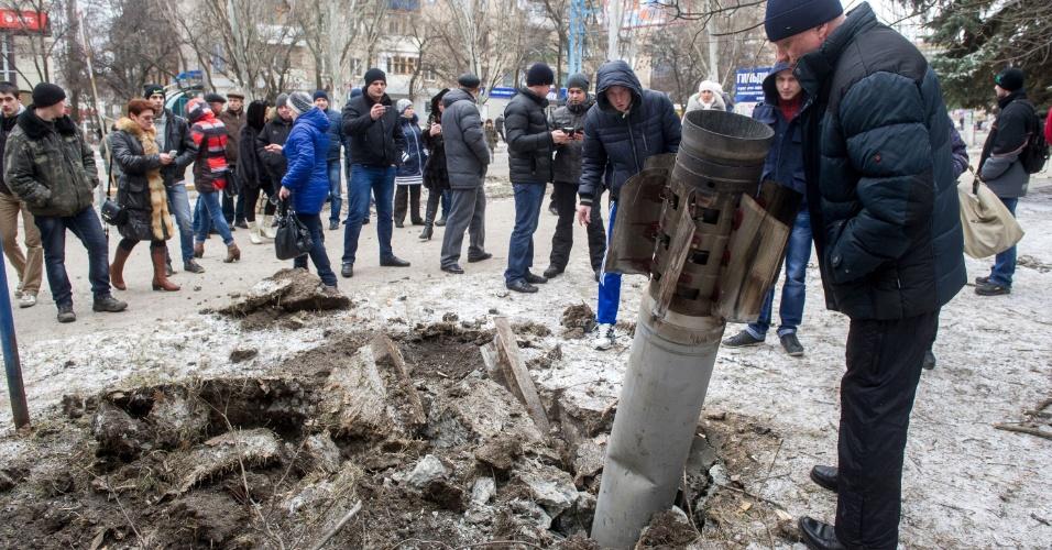 10.fev.2015 - Moradores da cidade de Kramotorsk observam um foguete que caiu no meio da praça após bombardeio na cidade ucraniana. Seis pessoas morreram e outras 21 ficaram feridas em um ataque ao quartel-general militar da ucrânia, segundo autoridades locais. O ataque também teria atingido áreas residenciais de Kramatorsk, que estaria sob controle do governo de Kiev