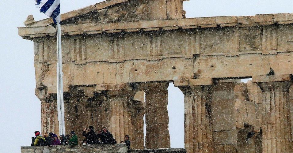 10.fev.2015 - Turistas fotografam nesta terça-feira (10) neve que caiu sobre a cidade de Atenas do topo da Acrópolis, na Grécia