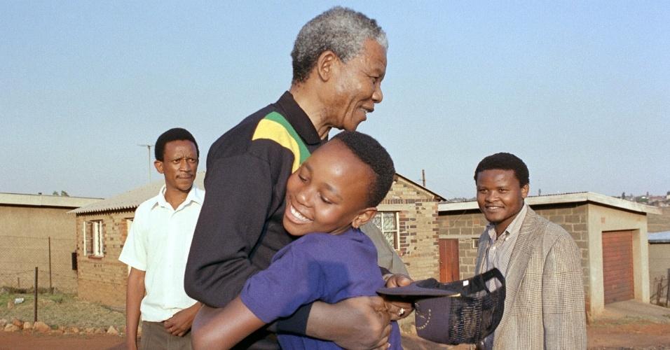 Em foto de outubro de 1990, Mandela é abraçado por criança sul-africana no Soweto, bairro em que morou nos tempos de ativismo