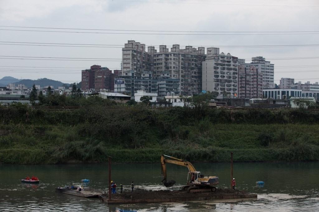 11.fev.2015 - Equipes de resgate desenterram lama do leito do rio Keelung durante as buscas pelo último corpo de vítima do acidente de avião da companhia TransAsia, em Taipé, em Taiwan, nesta quarta-feira (11). Dois corpos de passageiros foram encontrados ontem (10). O avião comercial transportava 58 pessoas a bordo quando se chocou com uma ponte logo após a decolagem e caiu em um rio no dia 4 de fevereiro