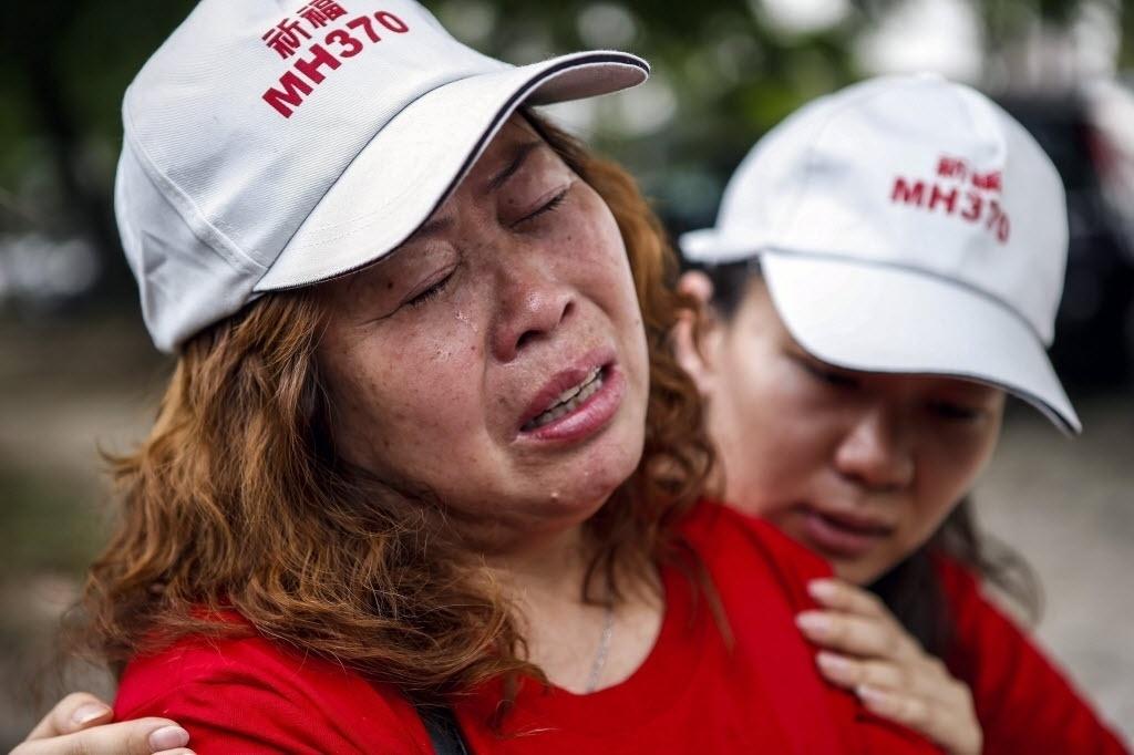 12.fev.2015 - Familiares de passageiros do voo MH370, da Malaysia Airlines, choram durante um protesto em frente à sede da companhia aérea em Subang, em Selangor (Malásia), nesta quinta-feira (12). A manifestação é contra a decisão do governo de declarar que os passageiros do avião que desapareceu em 8 de março de 2014 morreram