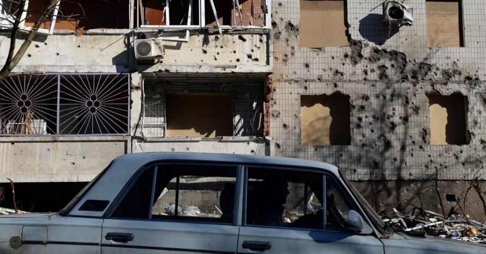 12.fev.2015 - Motorista passa na frente de um edifício destruído por bombardeios em Donetsk, no leste da Ucrânia, nesta quinta-feira (12). O presidente russo, Vladimir Putin, disse que ele e os líderes da França, Alemanha e Ucrânia entraram em acordo sobre a retirada das armas pesadas da Ucrânia e um cessar-fogo a partir de 15 de fevereiro