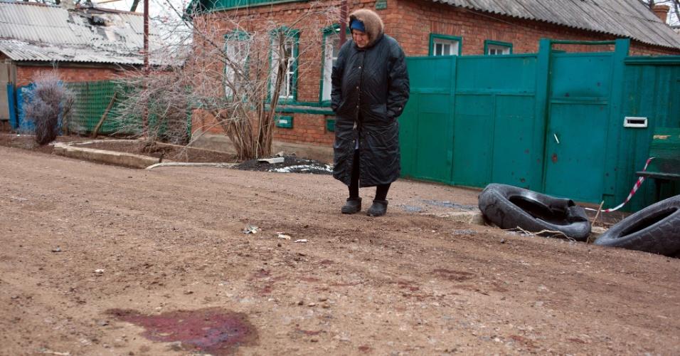 14.fev.2015 - Idosa observa, neste sábado (14), o local em que um de seus vizinhos foi morto em um bombardeio realizado por separatistas na cidade de Artemivsk, no leste da Ucrânia, na sexta-feira (13). O local é controlado por forças ucranianas. O ataque acontece a poucas horas do início do cessar-fogo, na virada de sábado para domingo