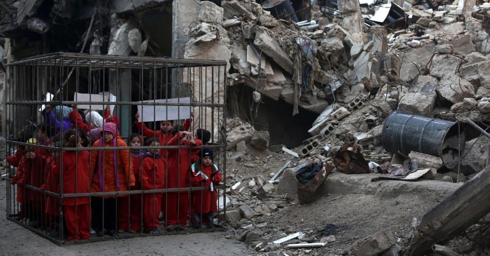 16.fev.2015 - Crianças síria vestem macacões laranja dentro de uma jaula colocada perto dos escombros de um edifício destruído por bombardeio das forças do governo sírio contra rebeldes no subúrbio de Douma, em Damasco, durante um protesto para denunciar o continuo assassinato de civis no conflito e a falha da comunidade internacional nas tentativas de parar a carnificina. Na ação, as crianças se vestem como o piloto jordaniano Maaz al-Kassasbeh, que foi queimado vivo por jihadistas do Estado Islâmico. A imagem foi registrada neste domingo (15) e divulgada nesta segunda-feira (16)