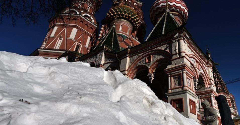 16.fev.2015 - Moradores caminham perto de um monte de neve em frente à catedral de São Basílio, na Praça Vermelha de Moscou, na Rússia, nesta segunda-feira (16)