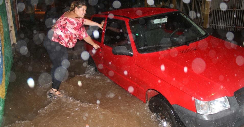 16.fev.2015 - Mulher tentar abrir a porta do carro na avenida Água Fria, no bairro do Santana, na zona norte de São Paulo, que ficou alagada após as fortes chuvas que atingiram a região na noite desta segunda-feira (16)