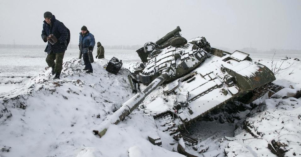 16.fev.2015 - Rebeldes da autoproclamada República Popular de Donetsk retiram partes de um tanque ucraniano destruído na cidade de Vuhlehirsk. Cinco soldados ucranianos foram mortos nas últimas 24 horas em combate com rebeldes pró-Rússia desde que o cessar-fogo entre as partes entrou em vigor