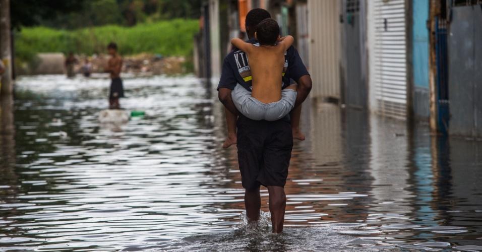 17.fev.2015 - Homem carrega criança nas costas enquanto caminha em rua alagada no bairro de Itaim Paulista, na zona leste de São Paulo, na tarde desta terça-feira (17). O temporal que caiu na região na noite da segunda-feira (16) transbordou o rio Tietê, o que causou alagamentos no bairro
