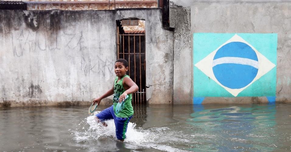 17.fev.2015 - Menino anda em rua alagada no bairro do Itaim Paulista, na zona leste de São Paulo, na tarde desta terça-feira (17). O temporal que caiu na região na noite da segunda-feira (16) transbordou o rio Tietê, o que causou alagamentos no bairro
