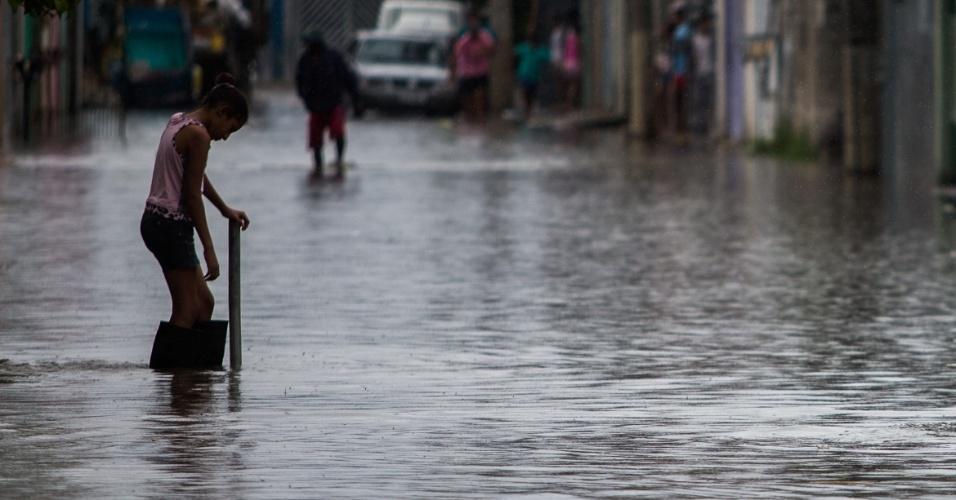 17.fev.2015 - Moradora tenta se locomover em rua alagada no bairro de Itaim Paulista, na zona leste de São Paulo, na tarde desta terça-feira (17). O temporal que caiu na região na noite da segunda-feira (16) transbordou o rio Tietê, o que causou alagamentos no bairro