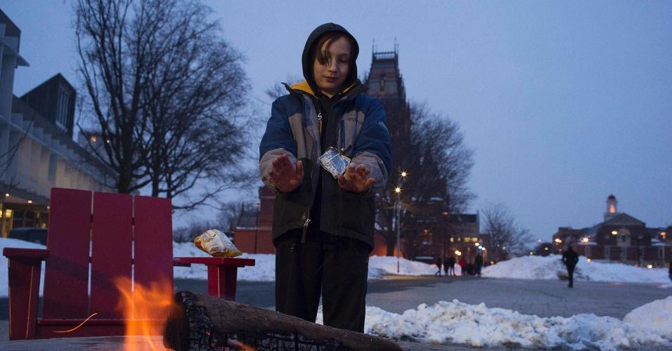 19.fev.2015 - Garoto aquece as mãos em uma fogueira na noite fria de inverno do lado de fora do Centro de Ciências da Universidade de Harvard em Cambridge, nos Estados Unidos.